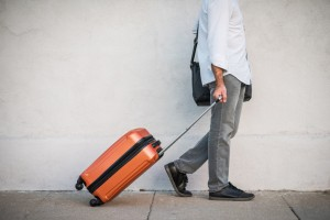 Male Traveler Rolling His Suitcase